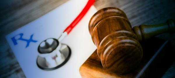 "gavel near a stethoscope on a paper that reads ""Rx"""