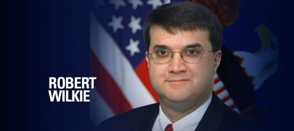 Image of Robert Wilkie in front of an American flag