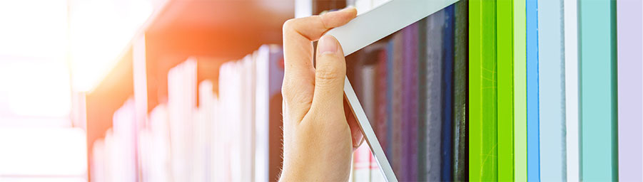 hand pulling an ipad from a shelf full of colorful books